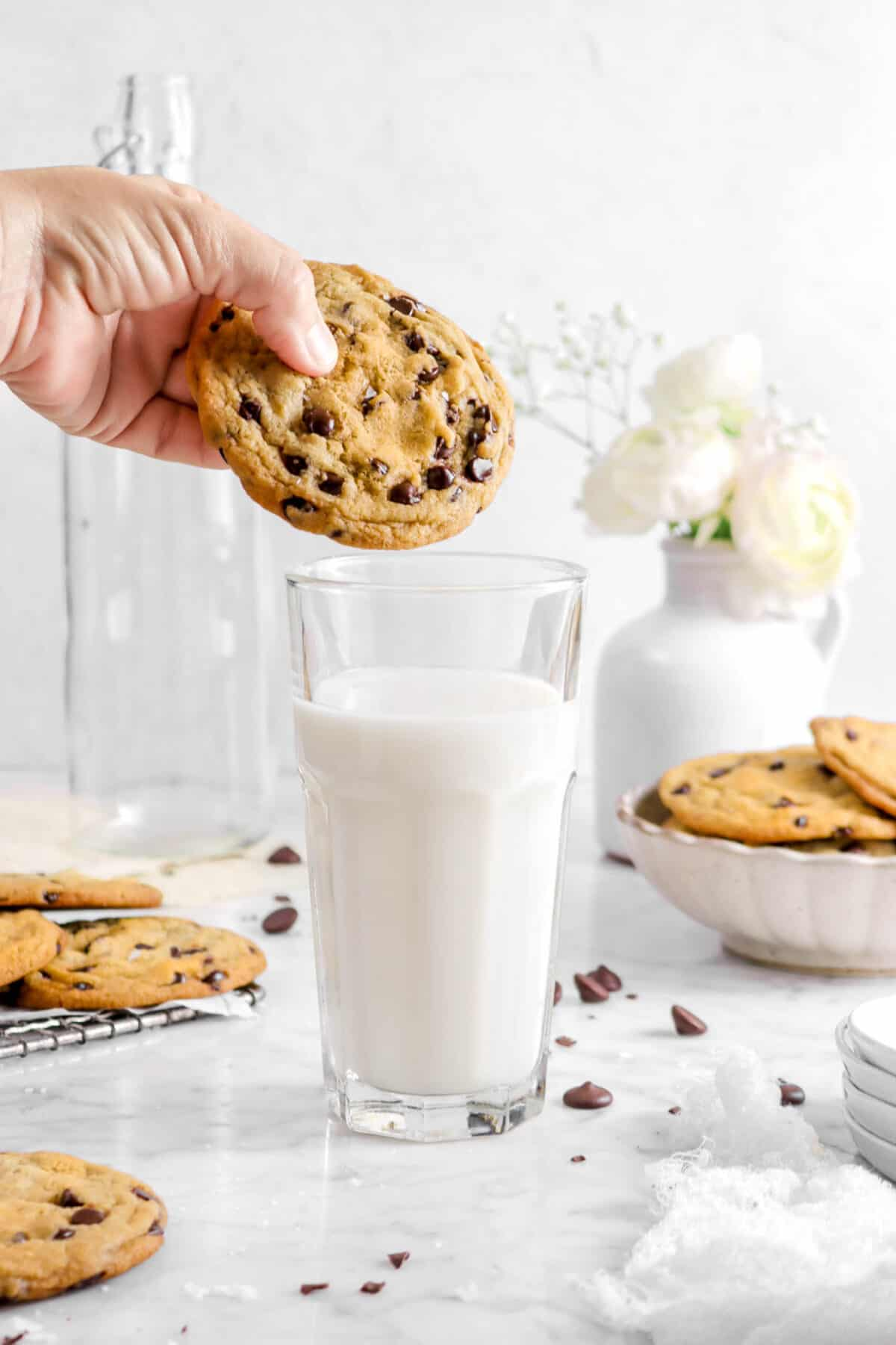 cookie being held over glass milk with flowers and more cookies behind