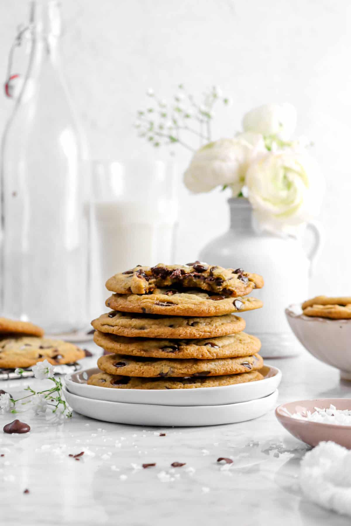 six stacked chocolate chip cookies with a bite taken out of one with a flowers and a glass of milk behind