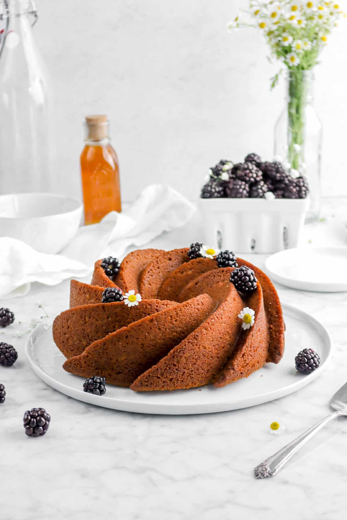 blackberry apple spice cake on white plate with blackberries, flowers, and a jar of honey behind