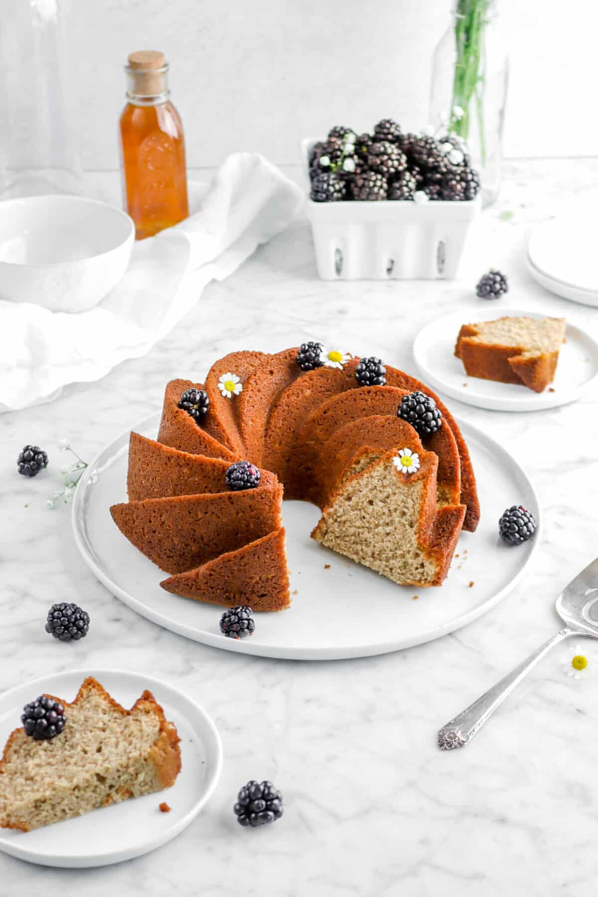 blackberry apple spice cake with a slice in front and behind, whole blackberries scattered around, chamomile flowers, a jar of honey, and a white napkin