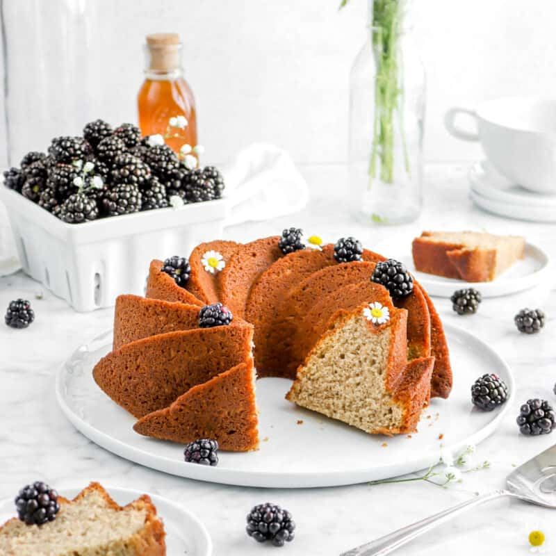 sliced blackberry apple spice cake on white plate with blackberries, flowers, and a jar of honey