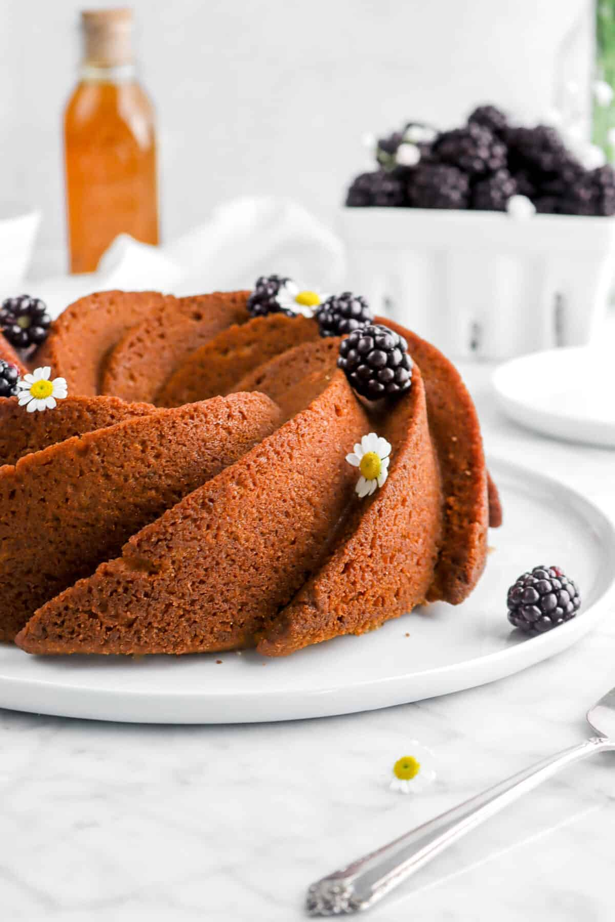 close up of spice cake on white plate with whole blackberries and flowers