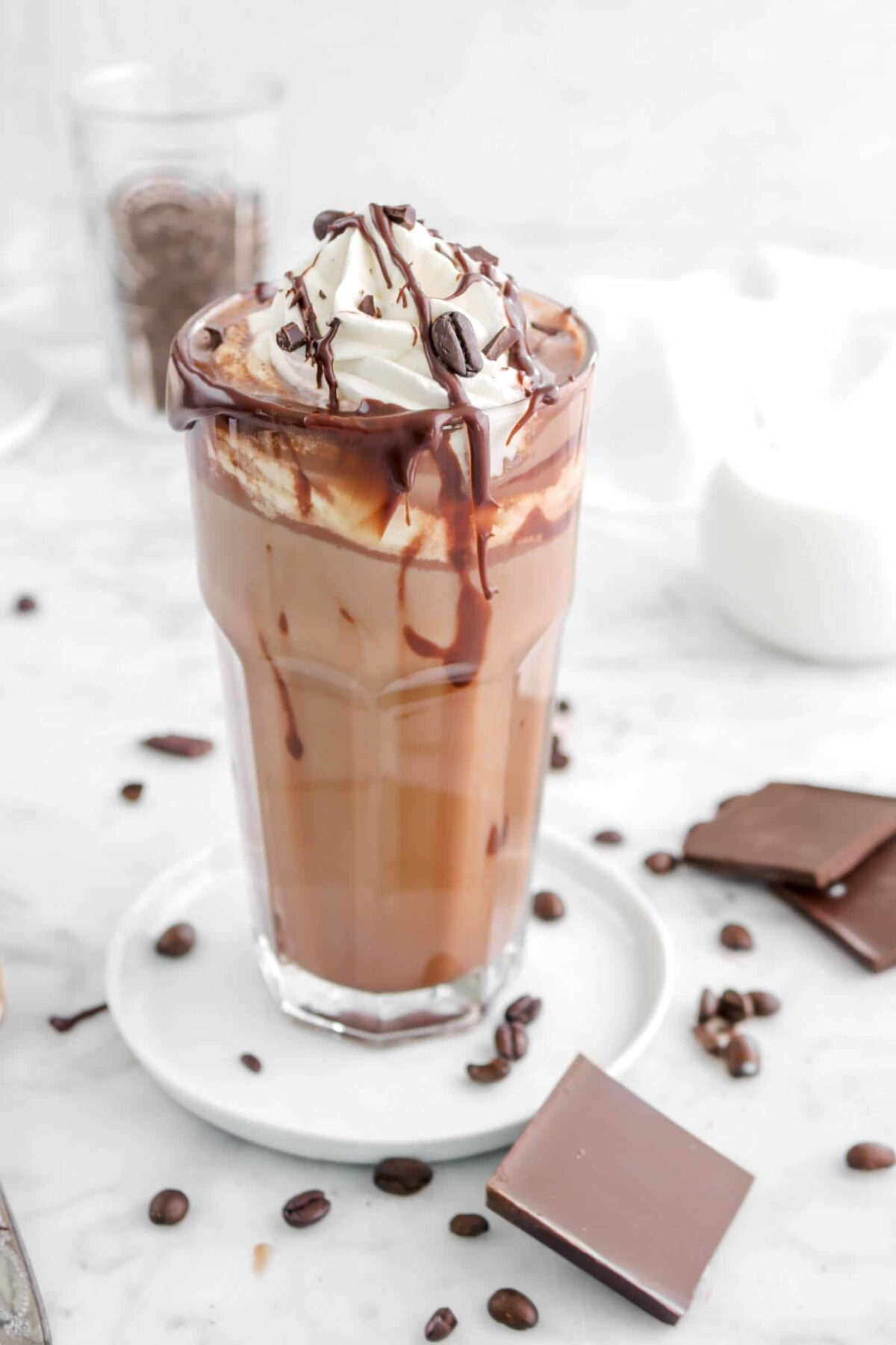 close up of mocha with chocolate sauce, coffee beans, and whipped cream