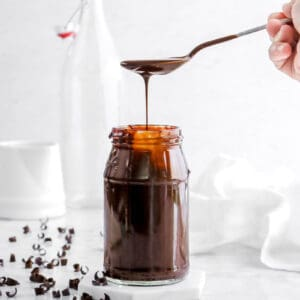 chocolate sauce with a spoon pouring sauce into the jar with chocolate curls, a white napkin, and glasses behind