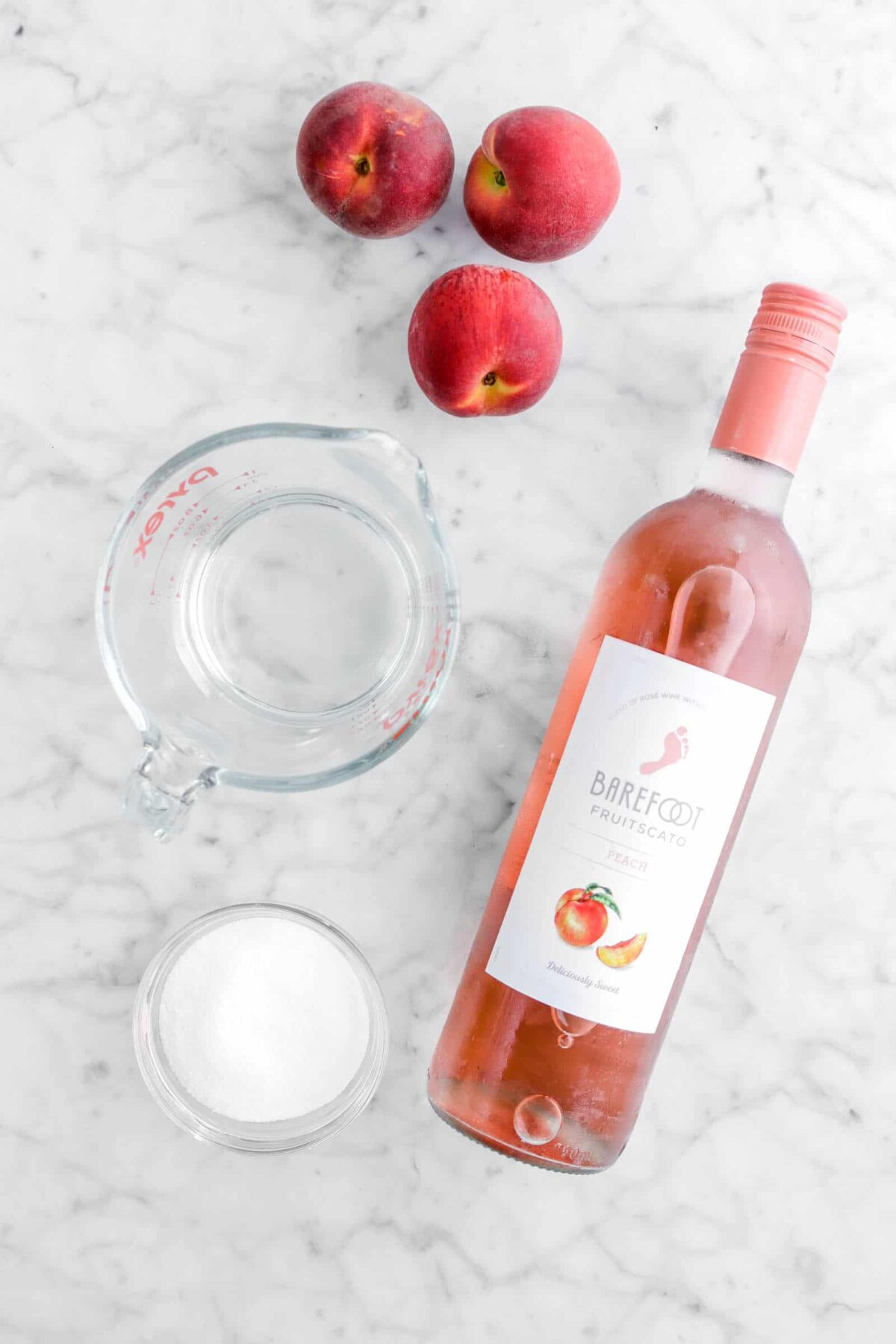 three peaches, schnapps, sugar, and bottle of peach moscato on marble counter
