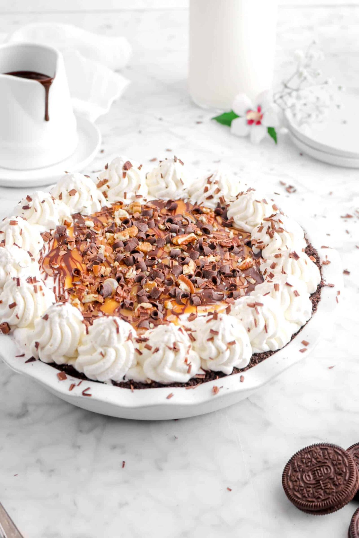 ice cream pie with flowers, glass of milk, and chocolate sauce