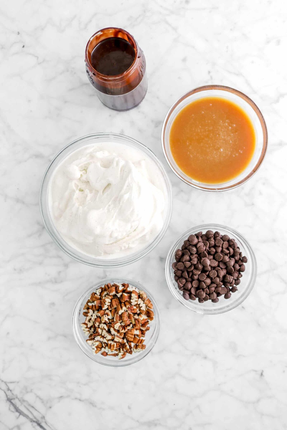 chocolate sauce, caramel sauce, ice cream, chocolate chips, and chopped pecans on marble counter