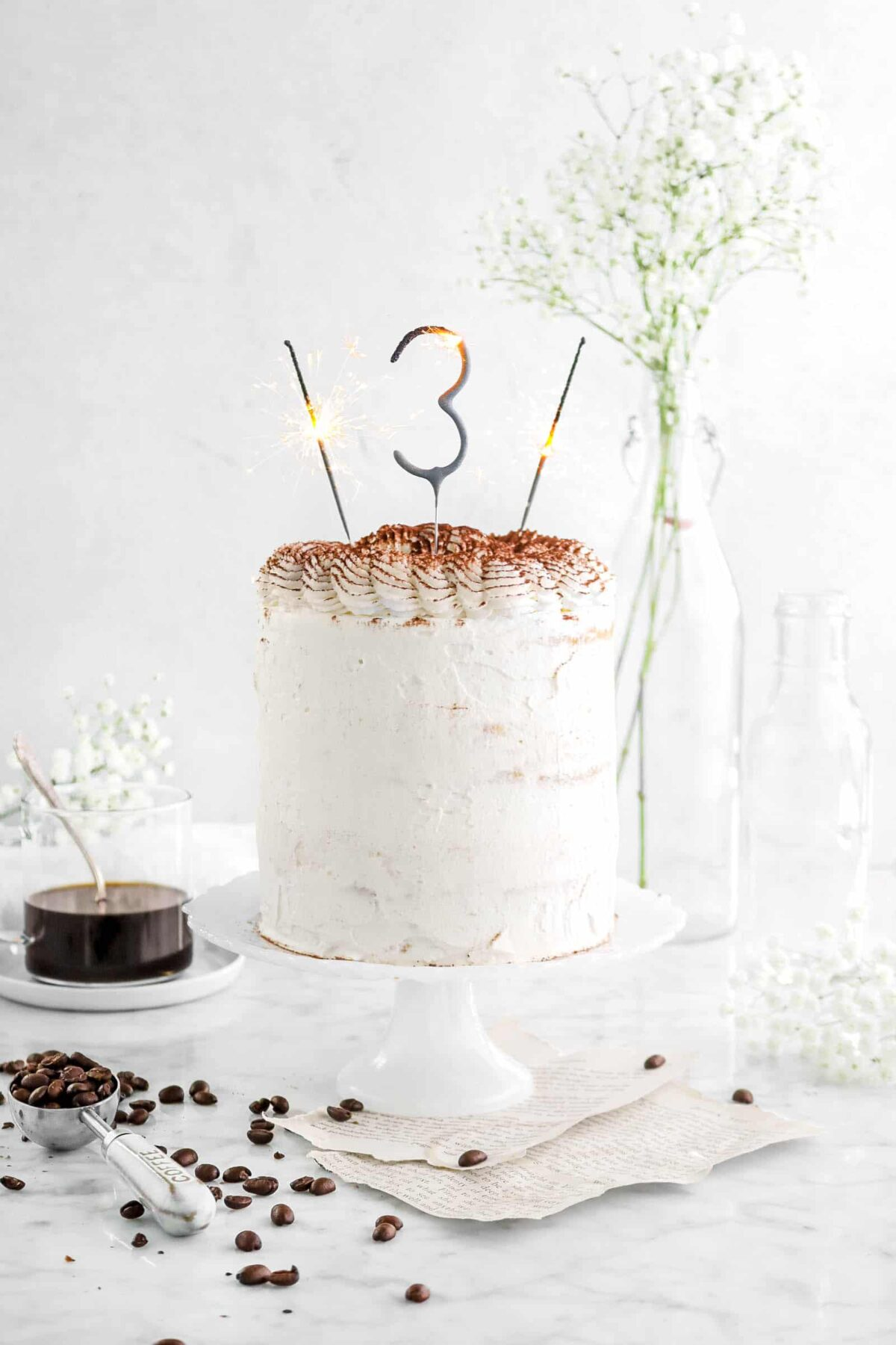 Tiramisu layer cake on cake stand with sparklers, book pages, coffee beans, flowers, and a cup of coffee