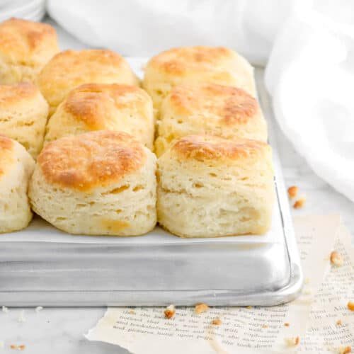 biscuits on an upside down sheet pan with crumbles and jar of honey