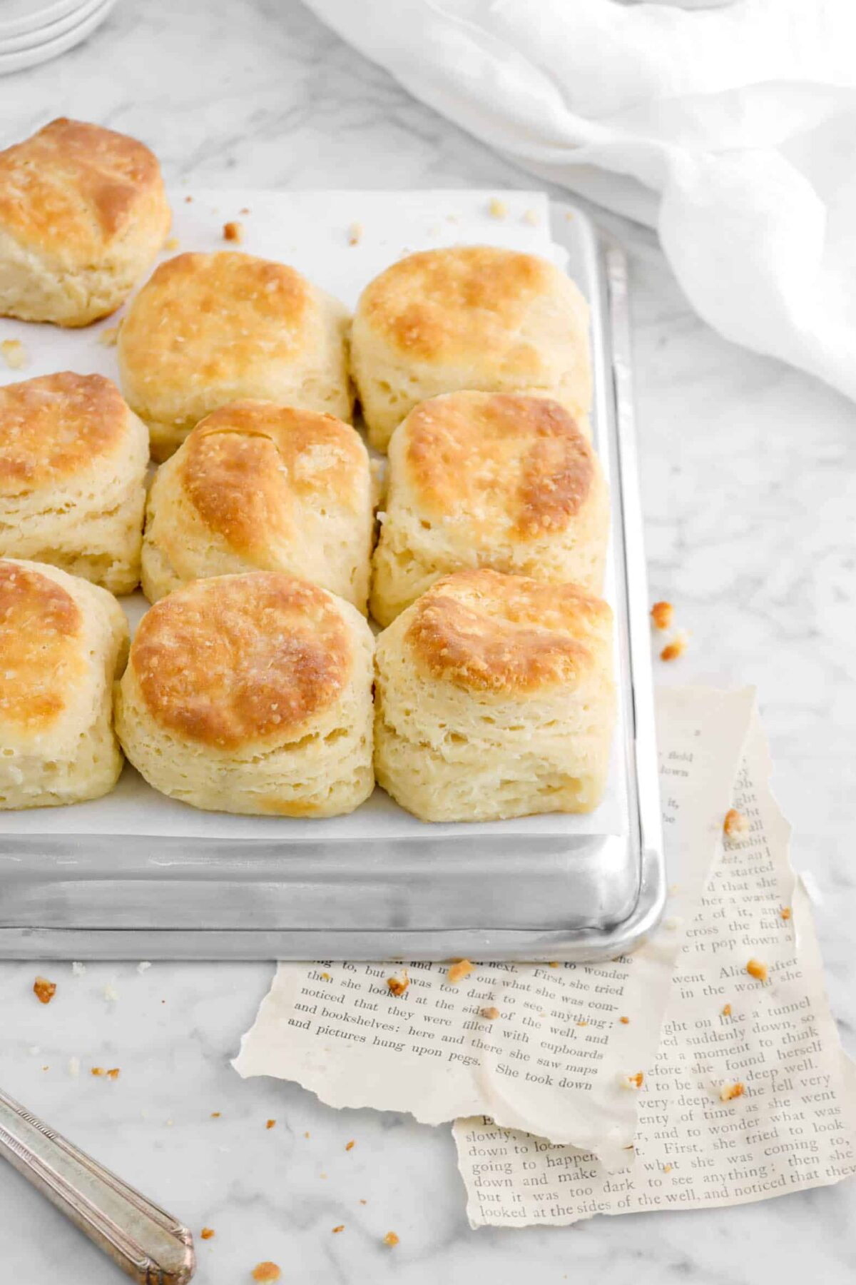 nine buttermilk biscuits on a sheet pan with book pages and white napkin