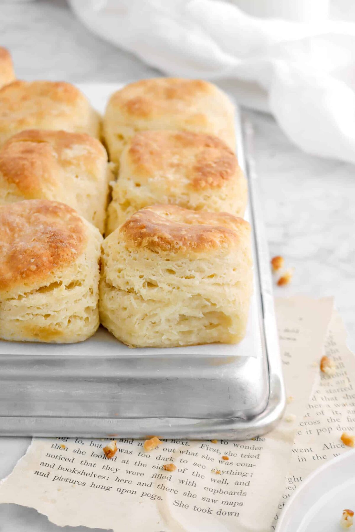 six biscuits on sheet pan with white napkin behind
