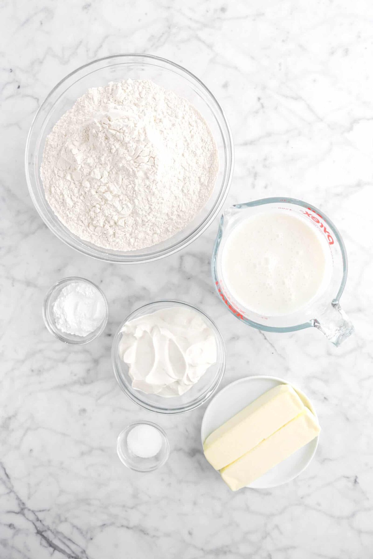 flour, buttermilk, baking powder, sour cream, salt, and two sticks of butter on marble counter