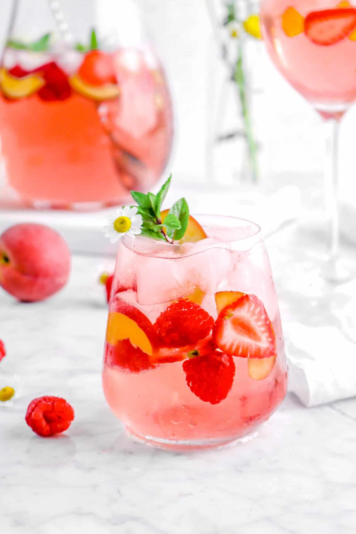 peach moscato with berries in the glass, a flower, and a sprig of mint