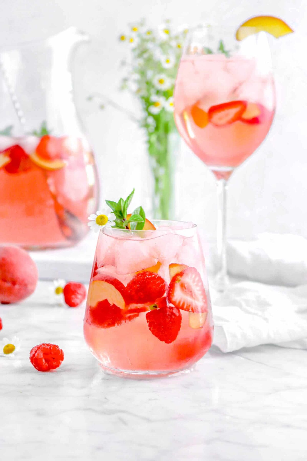 sangria with flowers, berries, and a sprig of mint