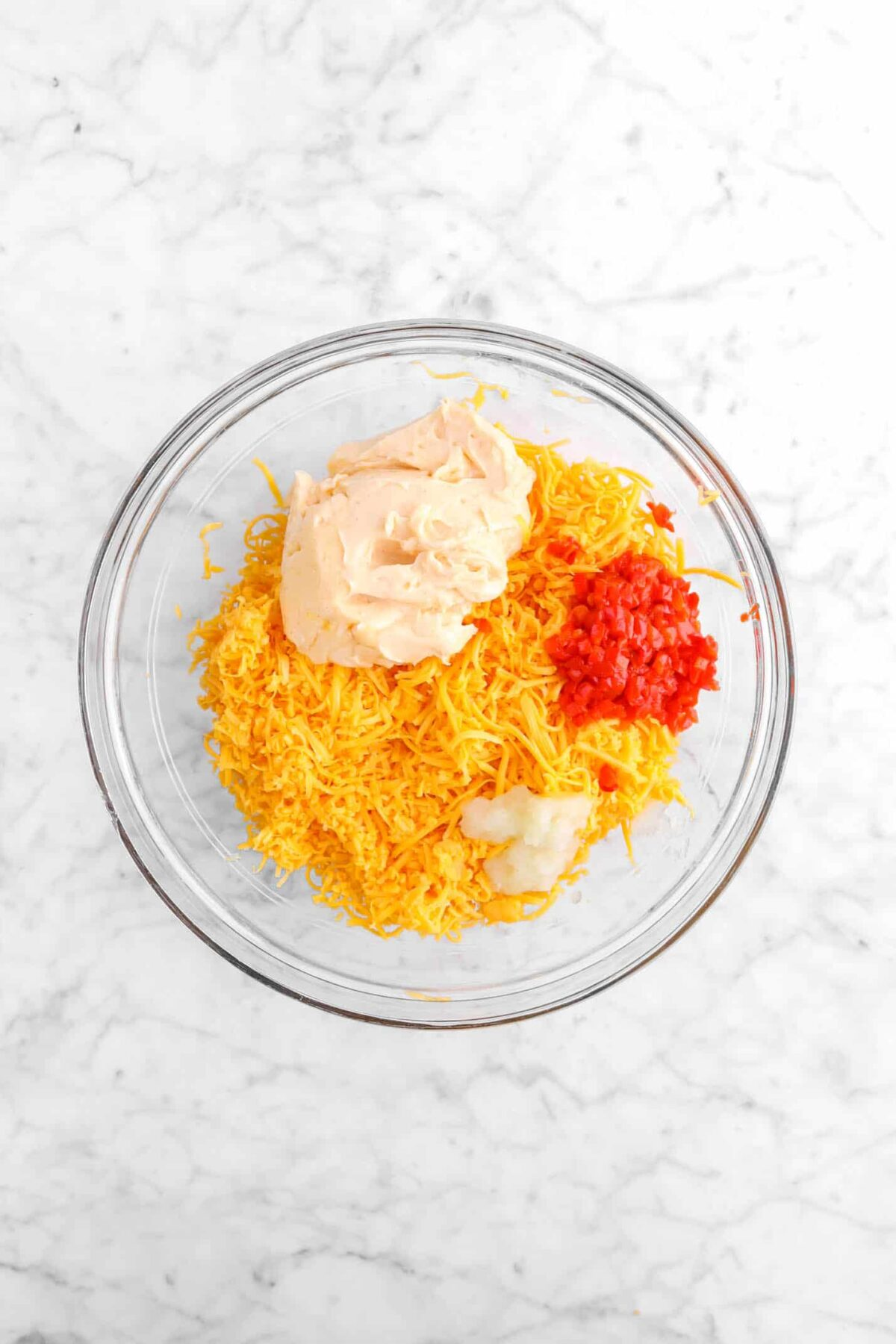 cheddar cheese, mayo, pimento and grated onion in a glass bowl
