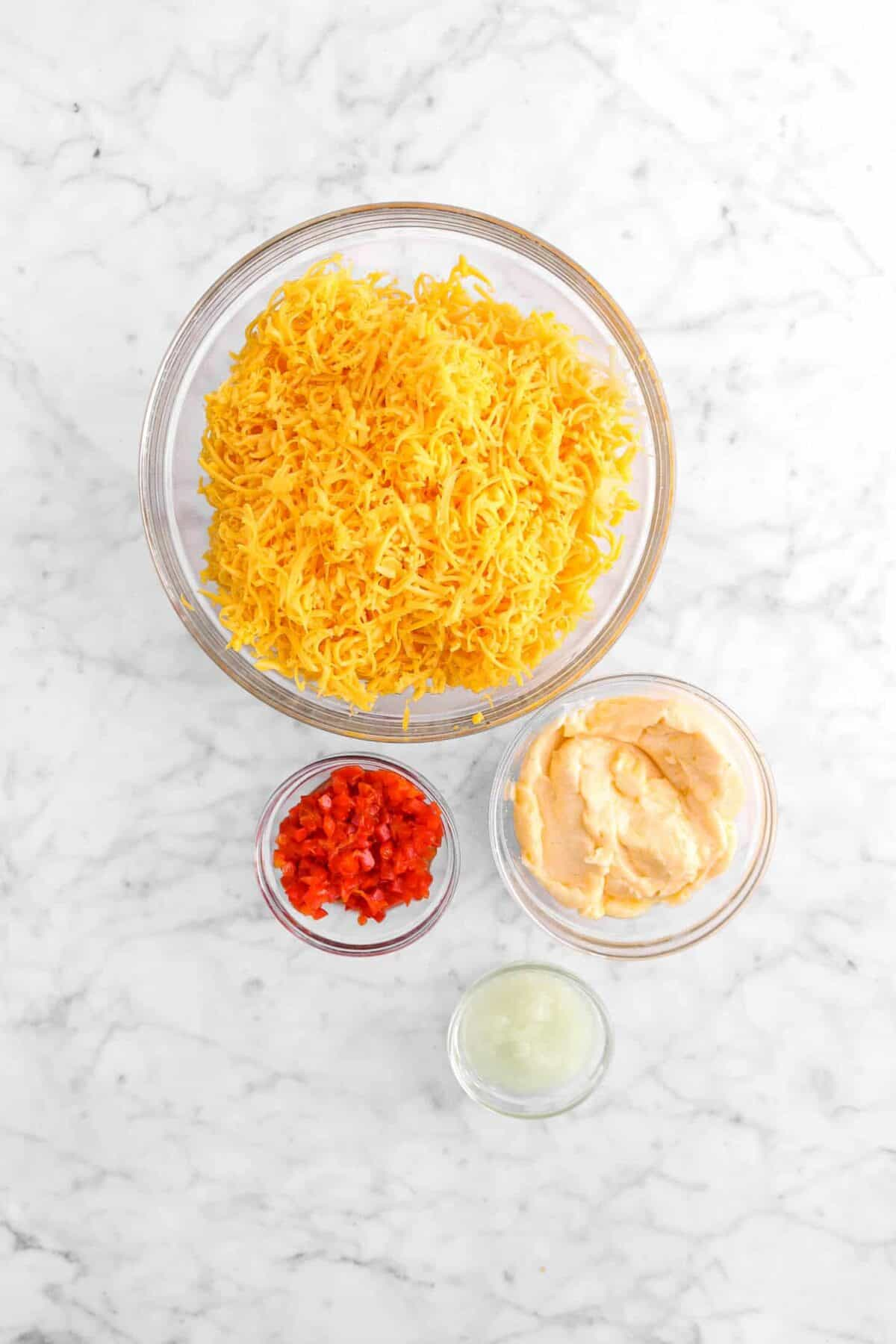 grated cheddar cheese, mayo, chopped pimento cheese, and grated onion in glass bowls