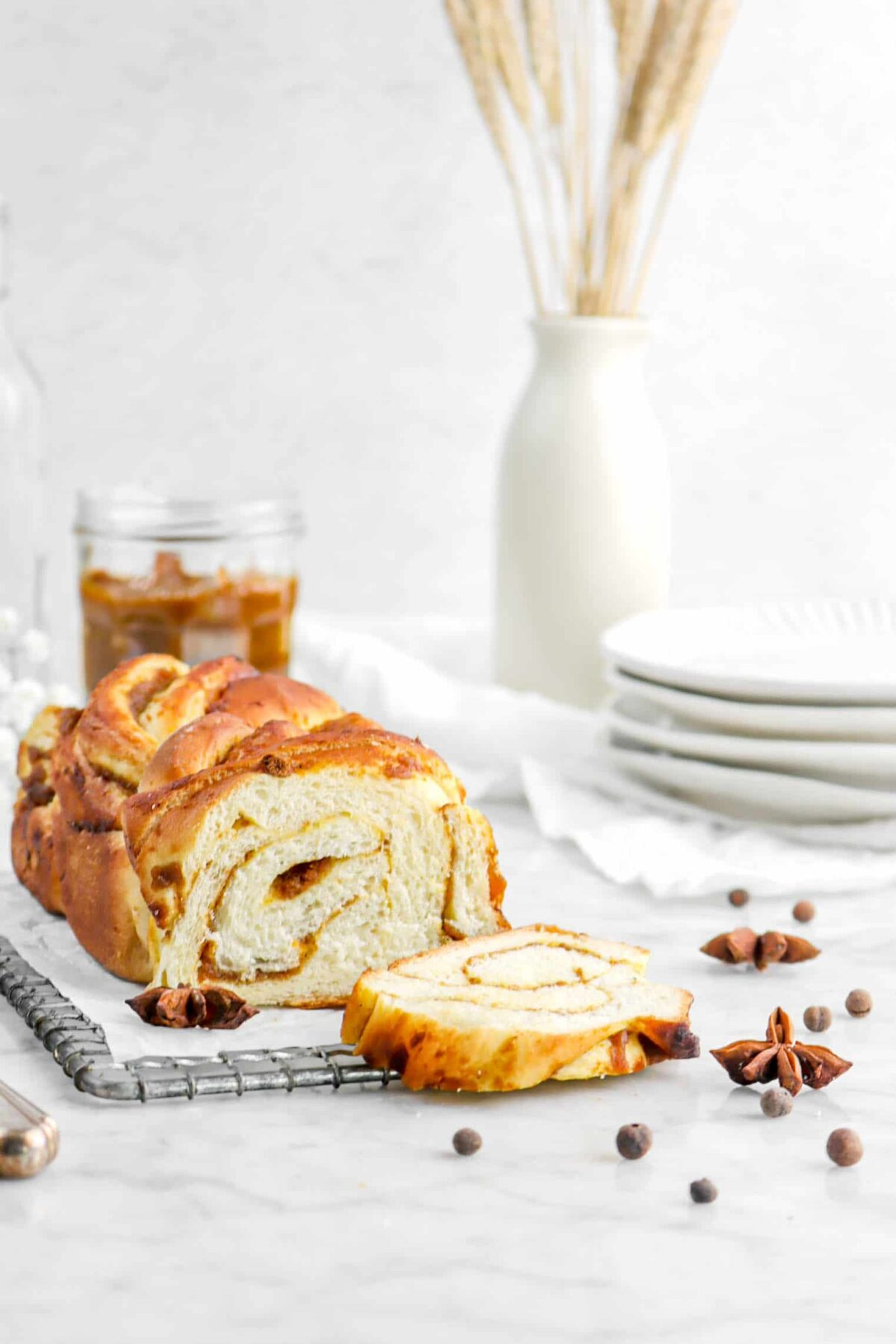pumpkin babka with slice laying in front with jar of dried wheat and a stack of plates behind