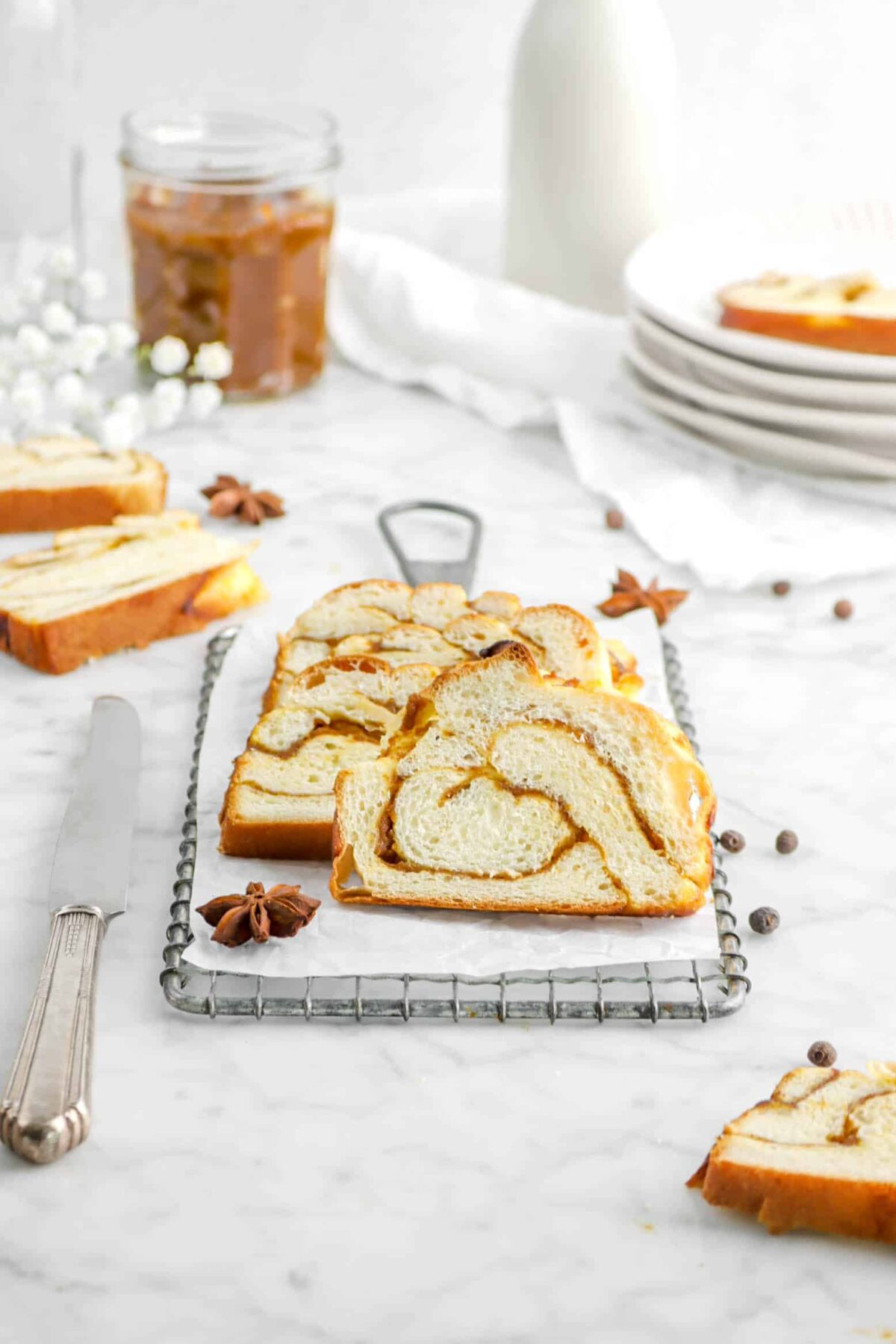 slices of babka on serving tray with whole spices, a knife, more slices around, and a jar of pumpkin butter