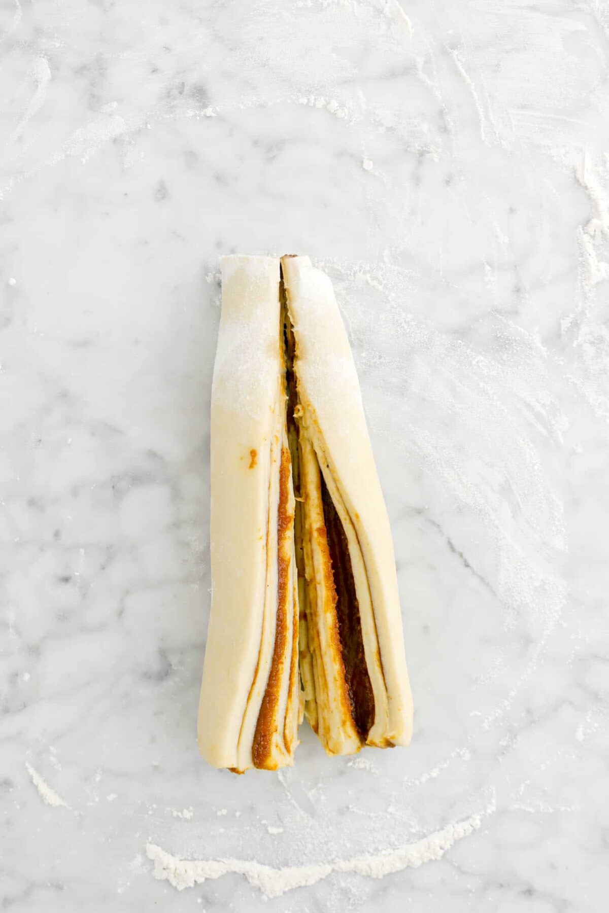 rolled dough cut in half lengthwise on marble counter