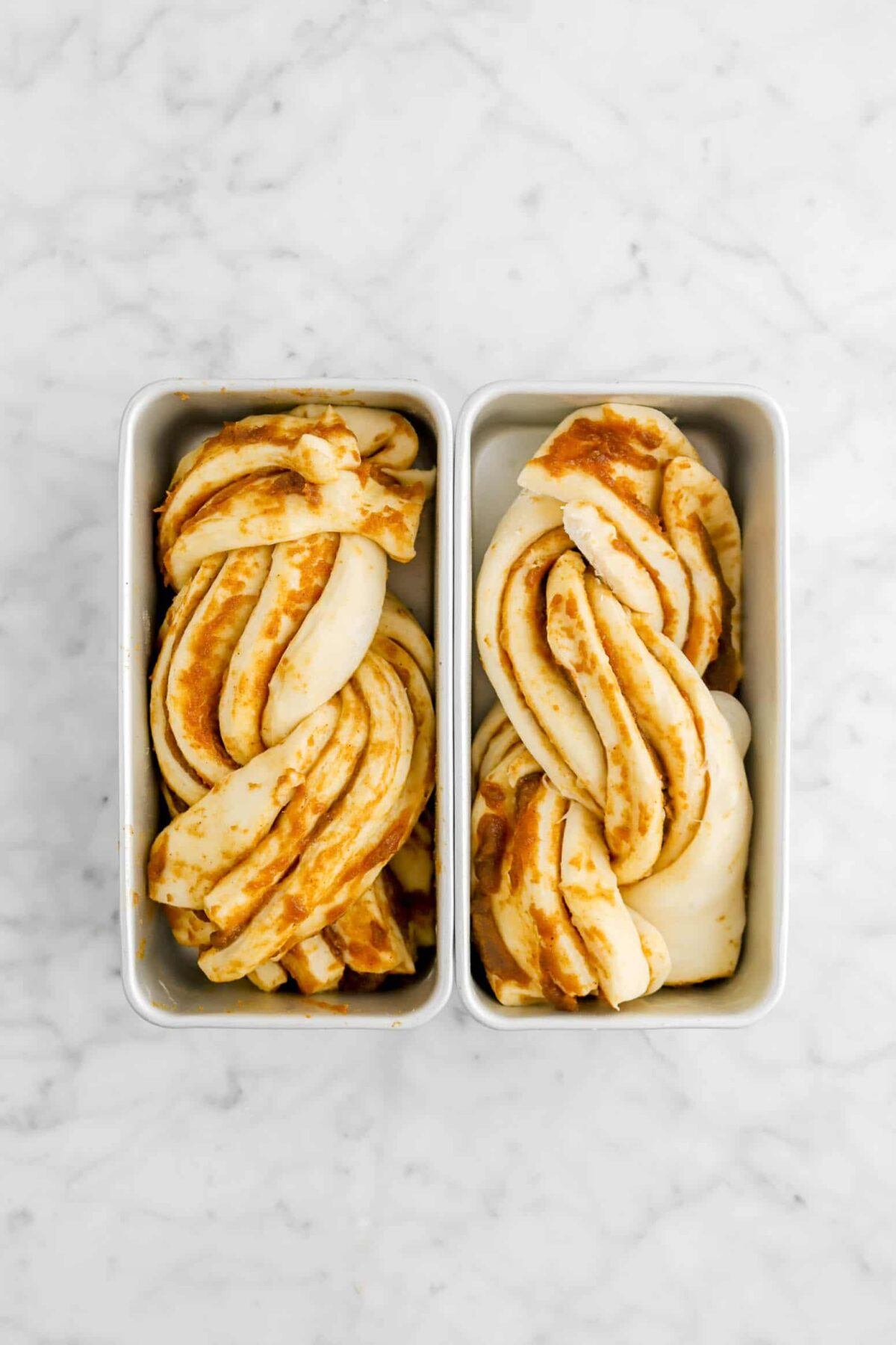 two pans of babka on marble counter