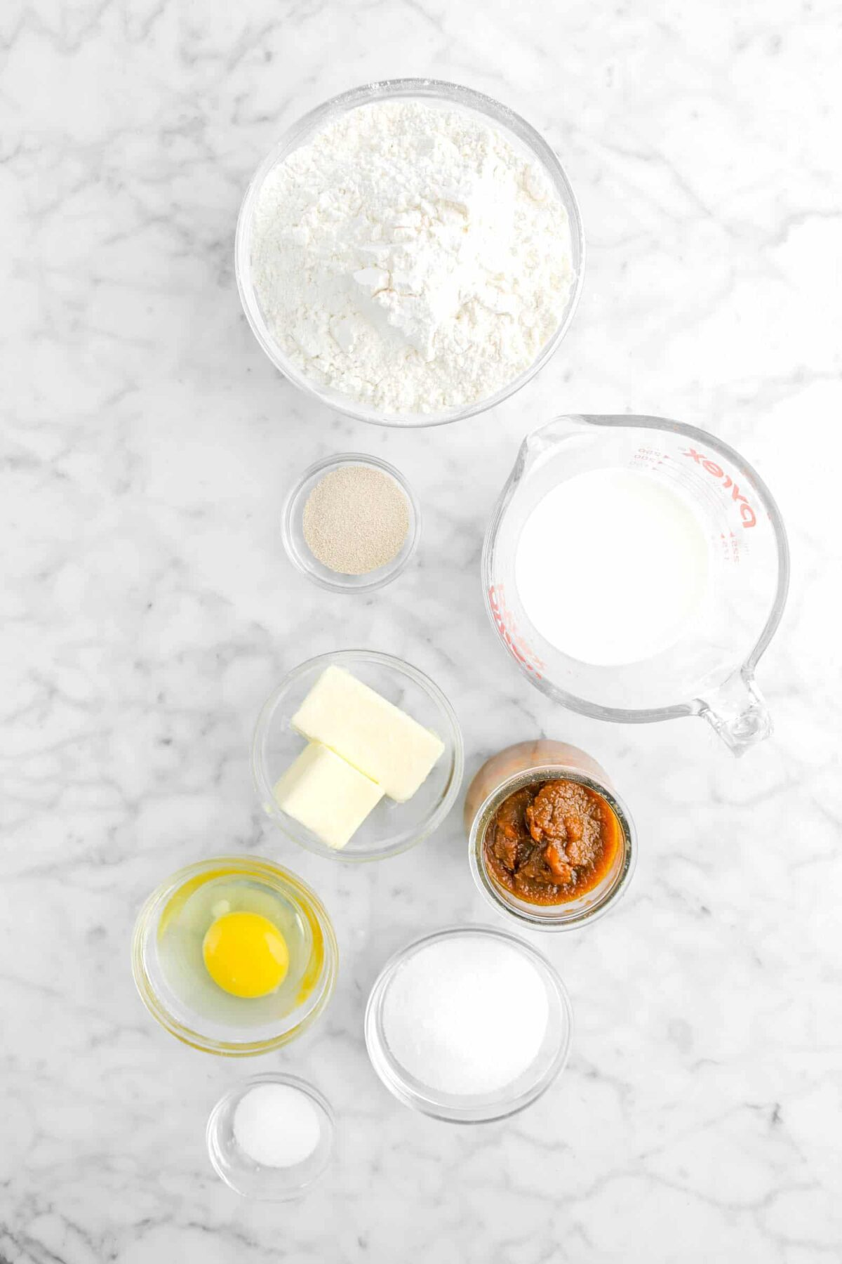 flour, yeast, milk, butter, pumpkin butter, egg, sugar, and salt on marble counter