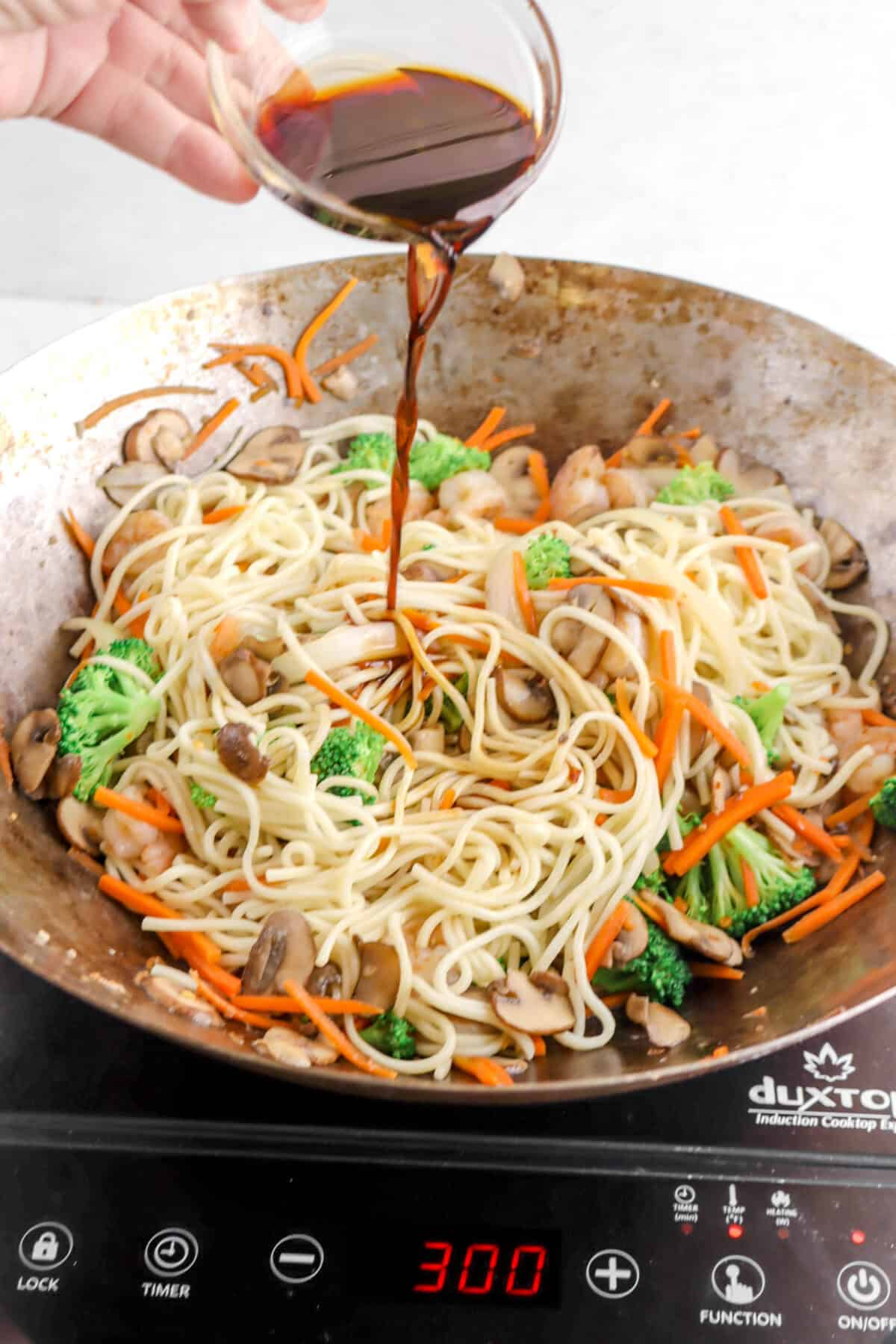 soy sauce being added to lo mein