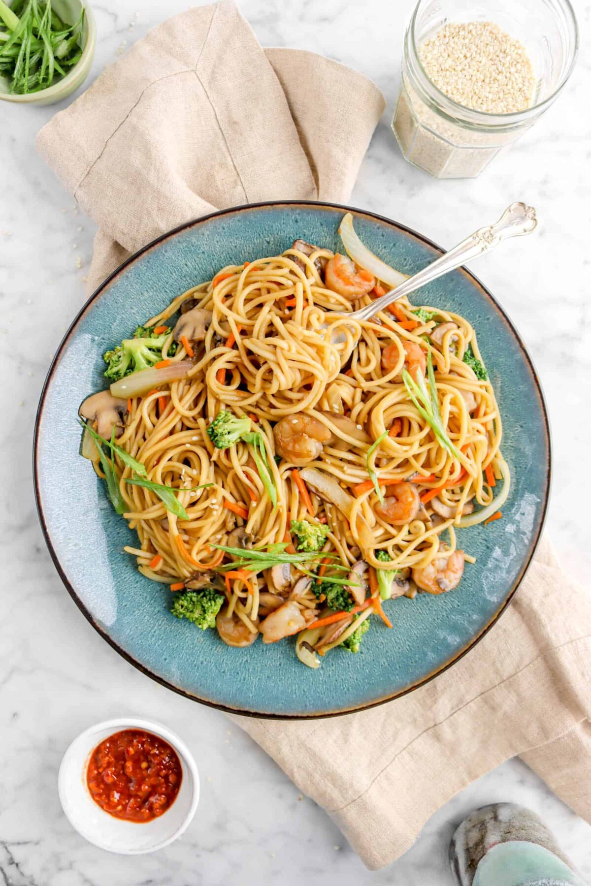 lo mein in blue plate on tan napkin with jar of sesame seeds, chili paste, and green onions