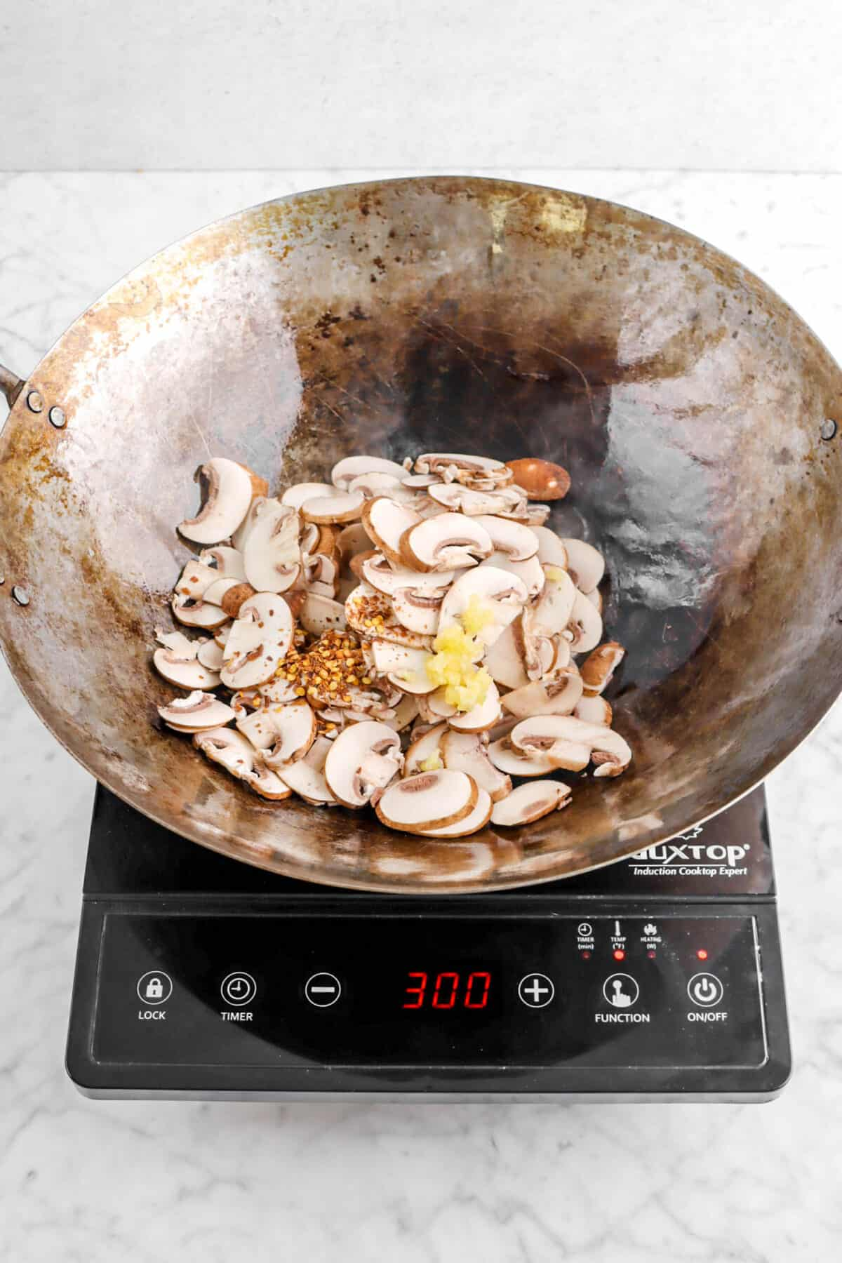 sliced mushrooms, red pepper flakes, and garlic in a wok