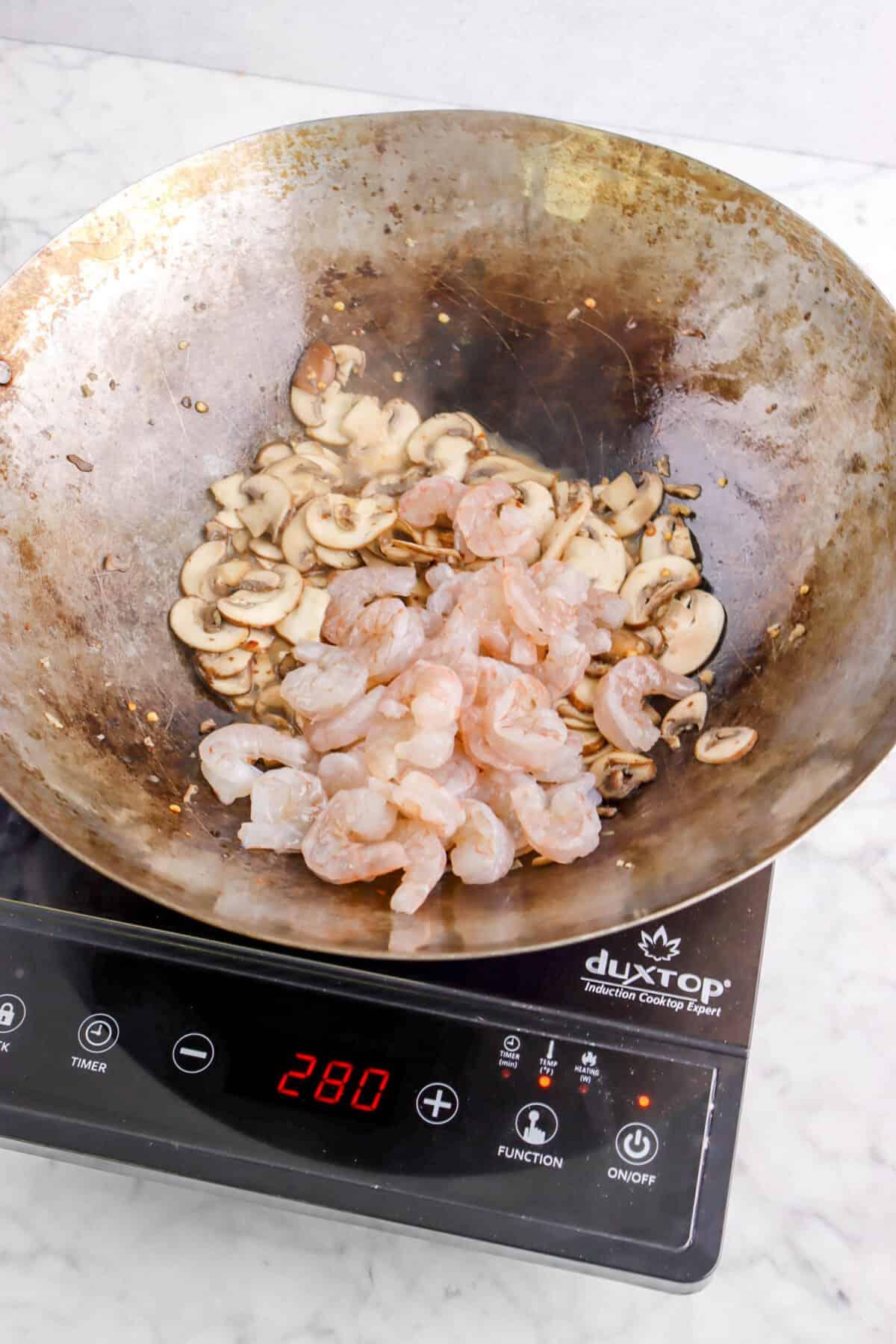 raw shrimp added to sautéed mushrooms