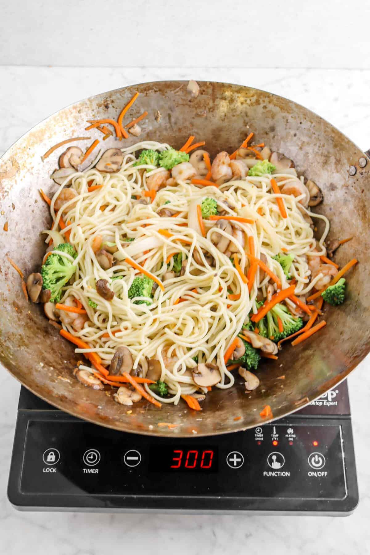 noodles added to vegetables and shrimp
