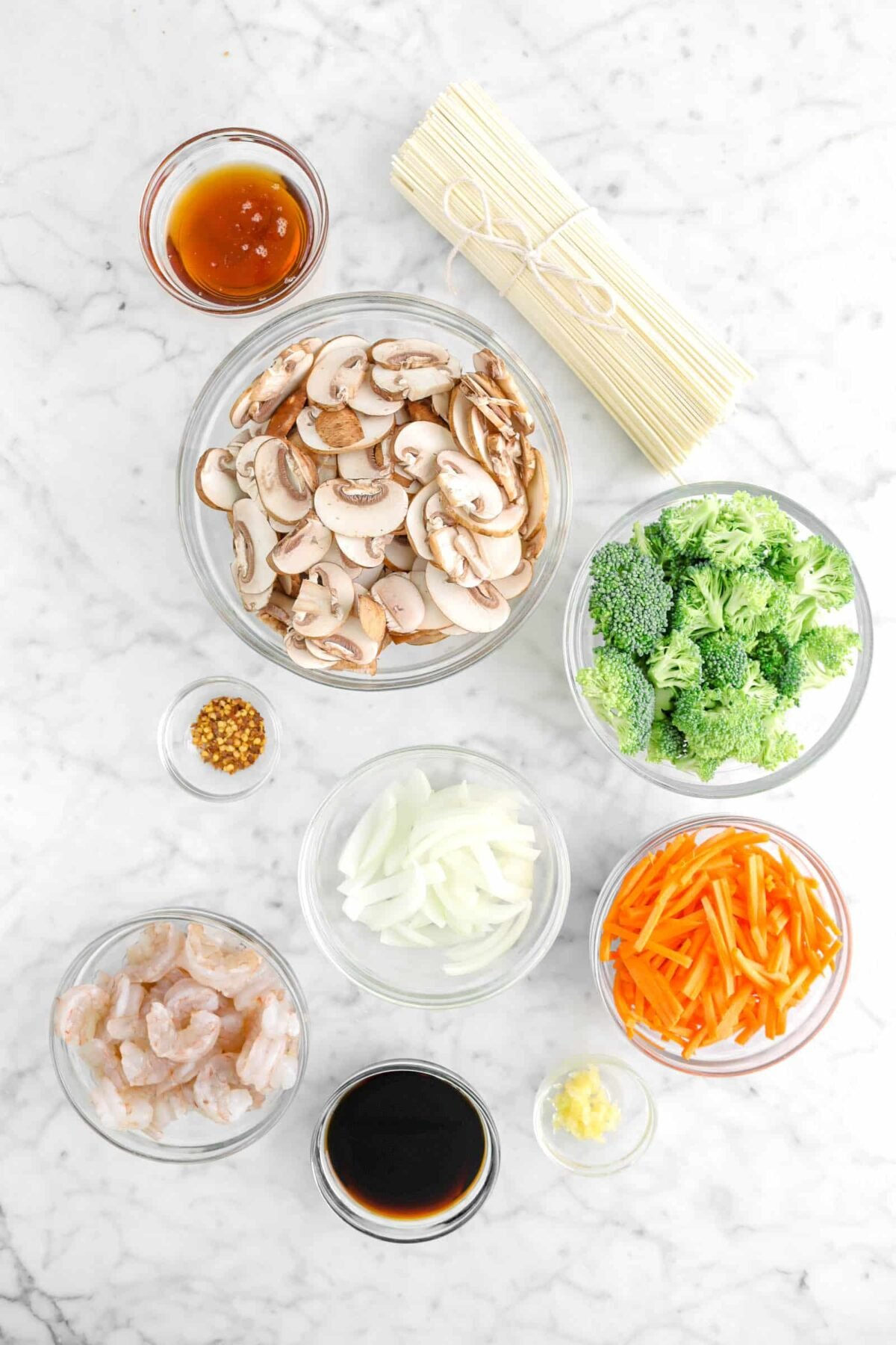 sesame oil, lo mein noodles, mushrooms, broccoli, red pepper flakes, onion, carrots, garlic, soy sauce, and shrimp on marble counter