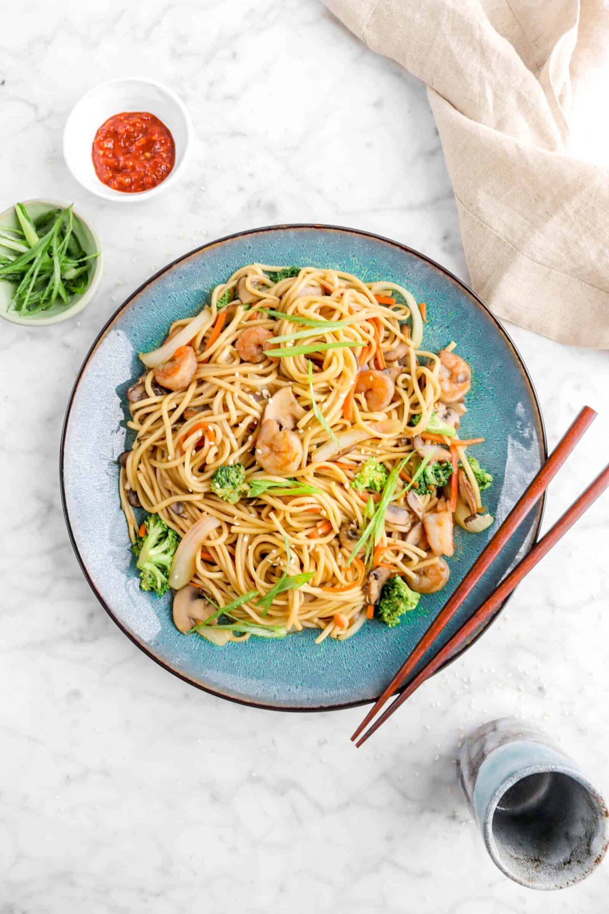 lo mein in blue bowl with chop sticks, toppings, and tan napkin