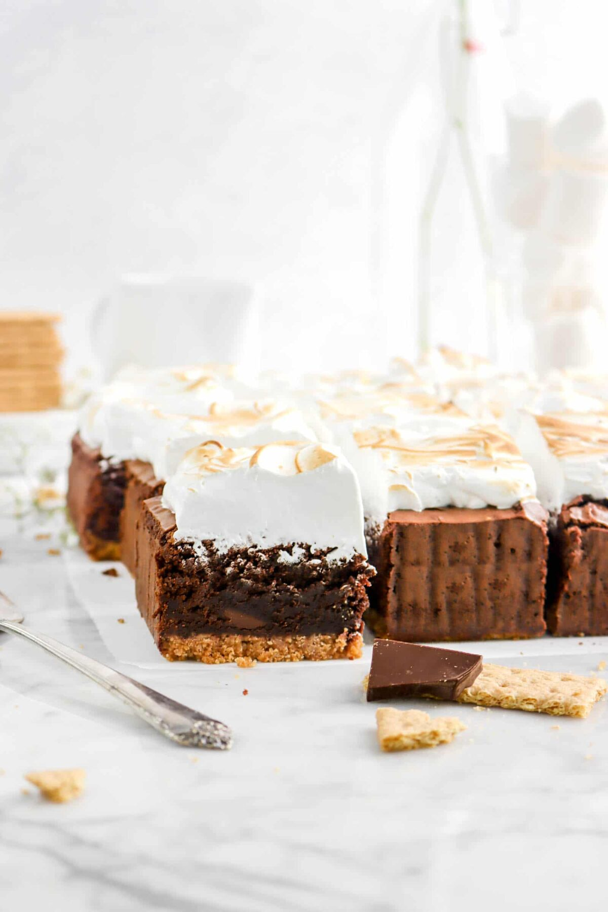 s'mores brownies on parchment paper with a glass of jumbo marshmallows, half of a graham cracker, and a piece of chocolate
