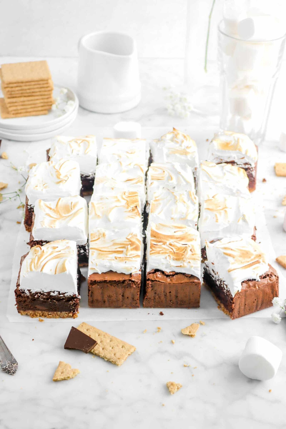 sixteen s'mores brownies on parchment paper with a glass of marshmallows, a stack of graham crackers, and flowers