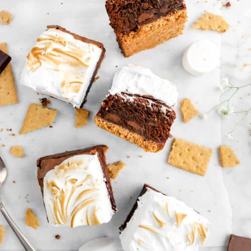 overhead shot of five s'more brownies with two on their side with graham cracker pieces, square chocolates, and flowers