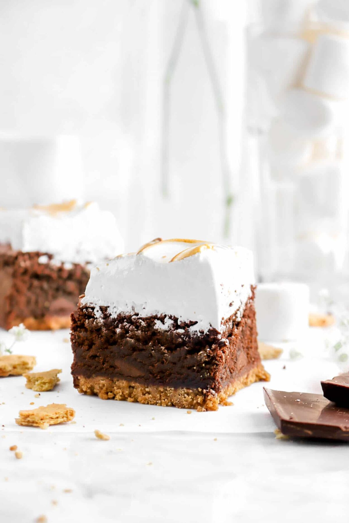s'more brownie n parchment with a glass of marshmallows and another brownie behind