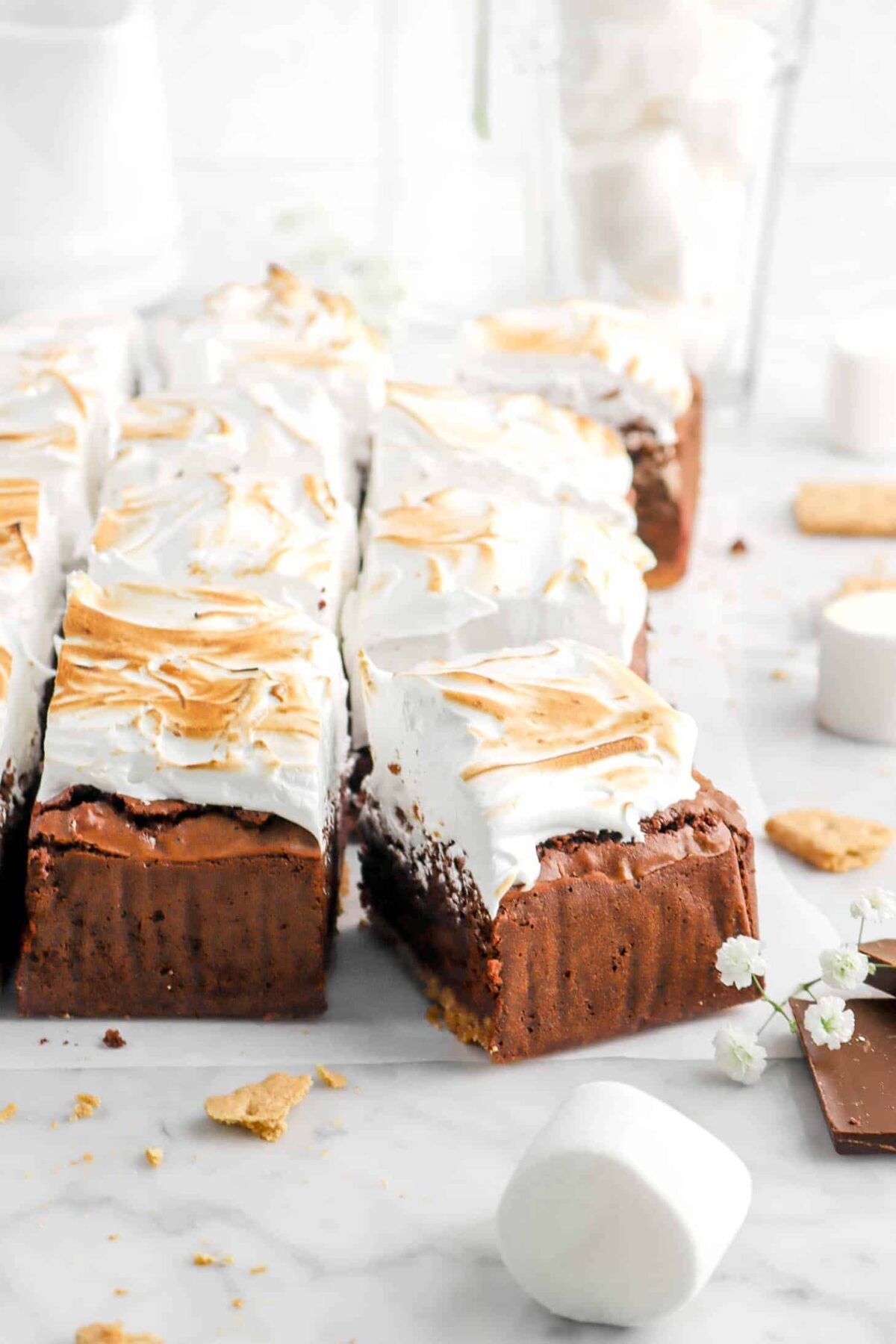 s'mores brownies on parchment with marshmallows, flowers, and graham cracker crumbs