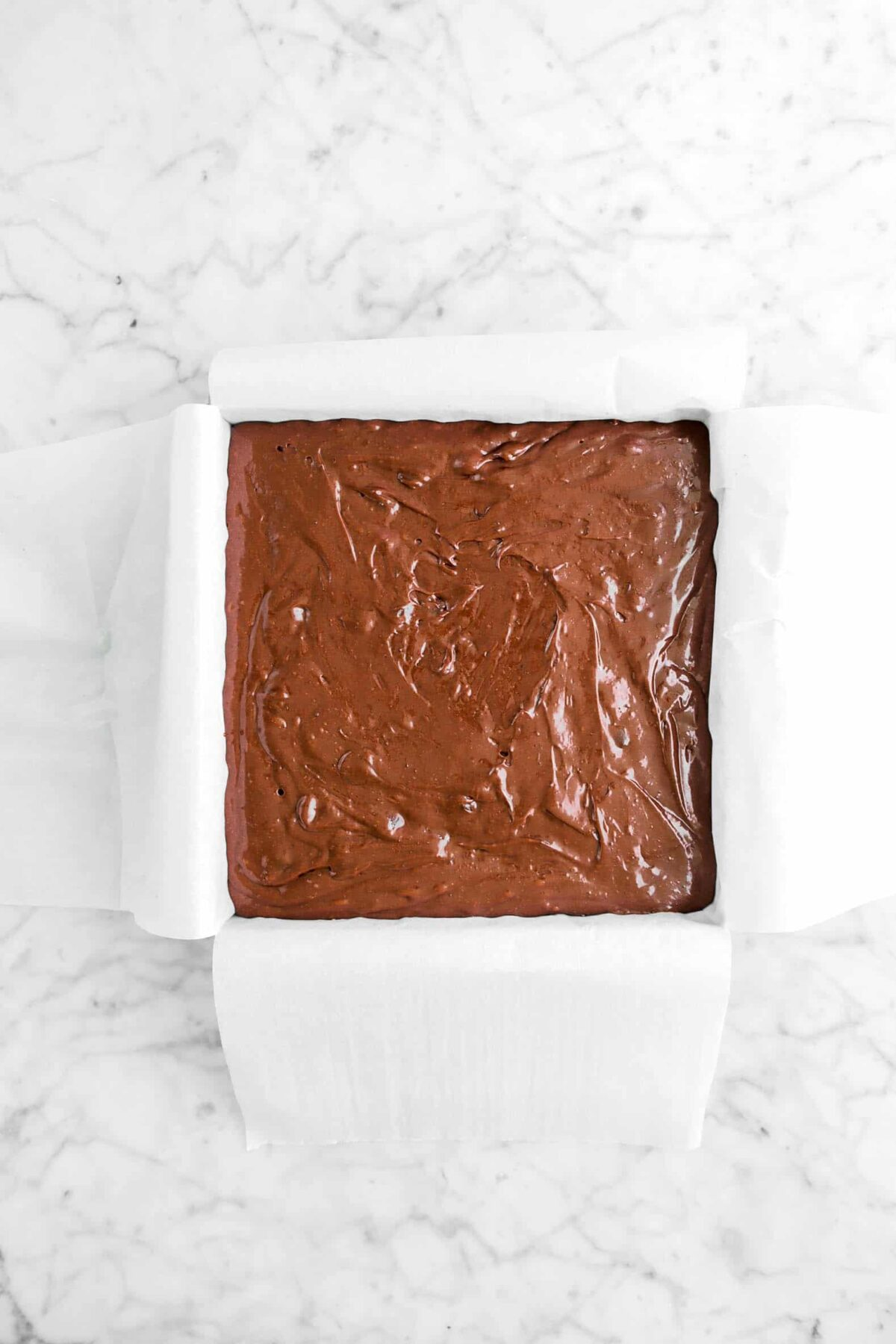 brownie batter in a lined rectangular pan