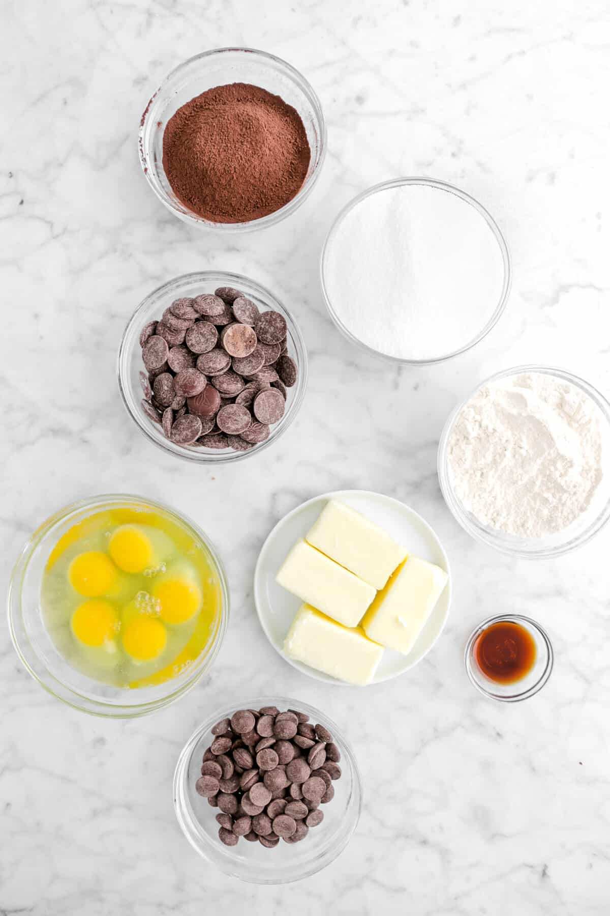cocoa powder, sugar, chocolate chips, flour, butter, eggs, and vanilla on marble counter