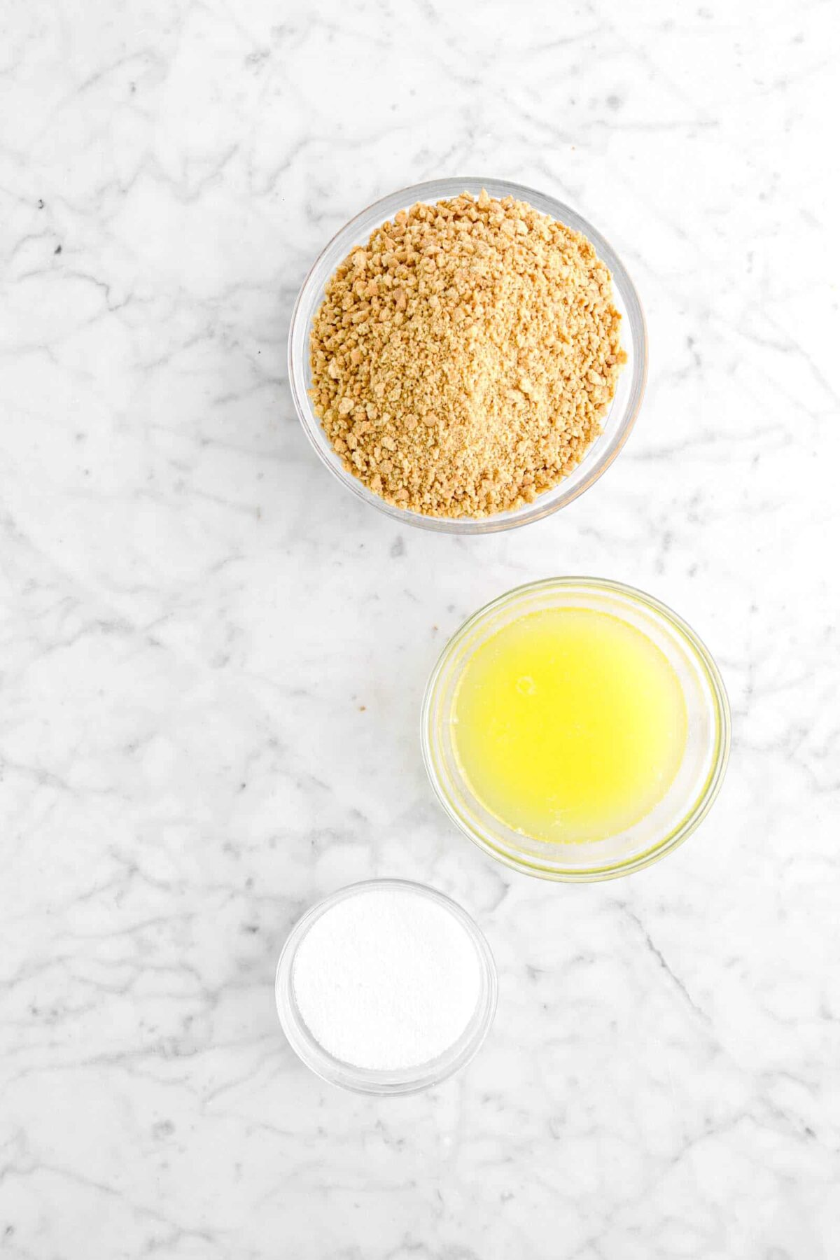 graham cracker crumbs, melted butter, and sugar on marble counter