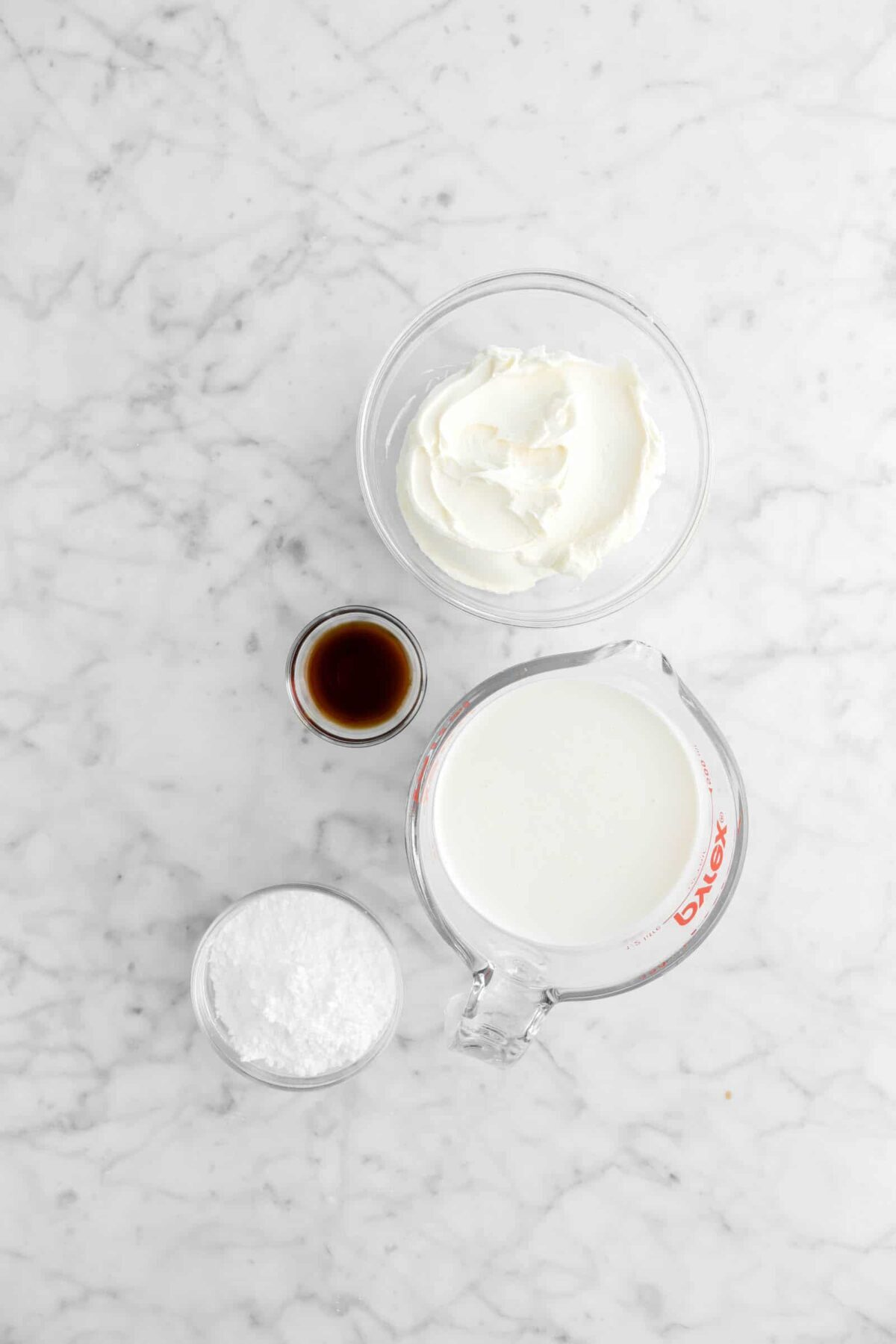 mascarpone, vanilla, heavy cream, and powdered sugar in glass bowls on a marble counter