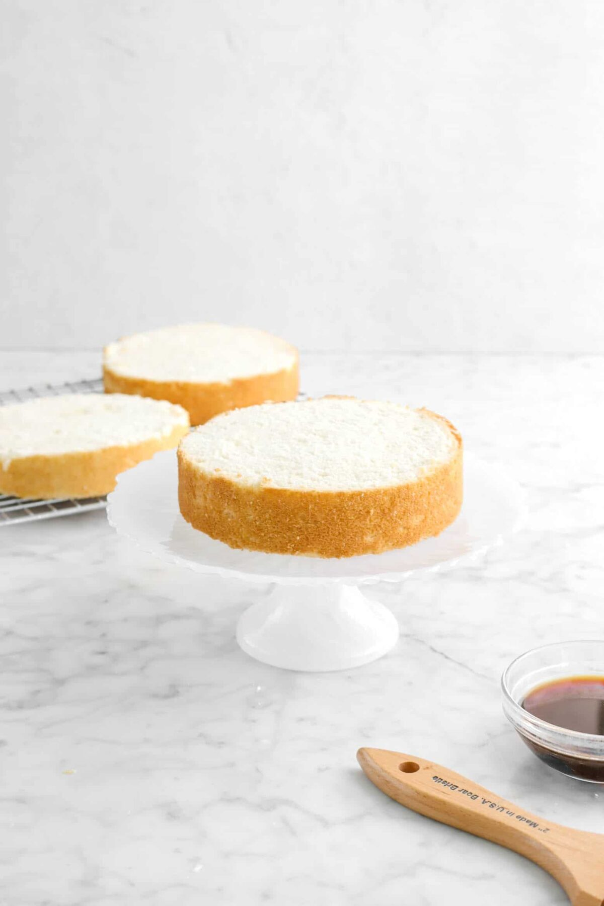 cake layer on white cake stand with two cake layers behind