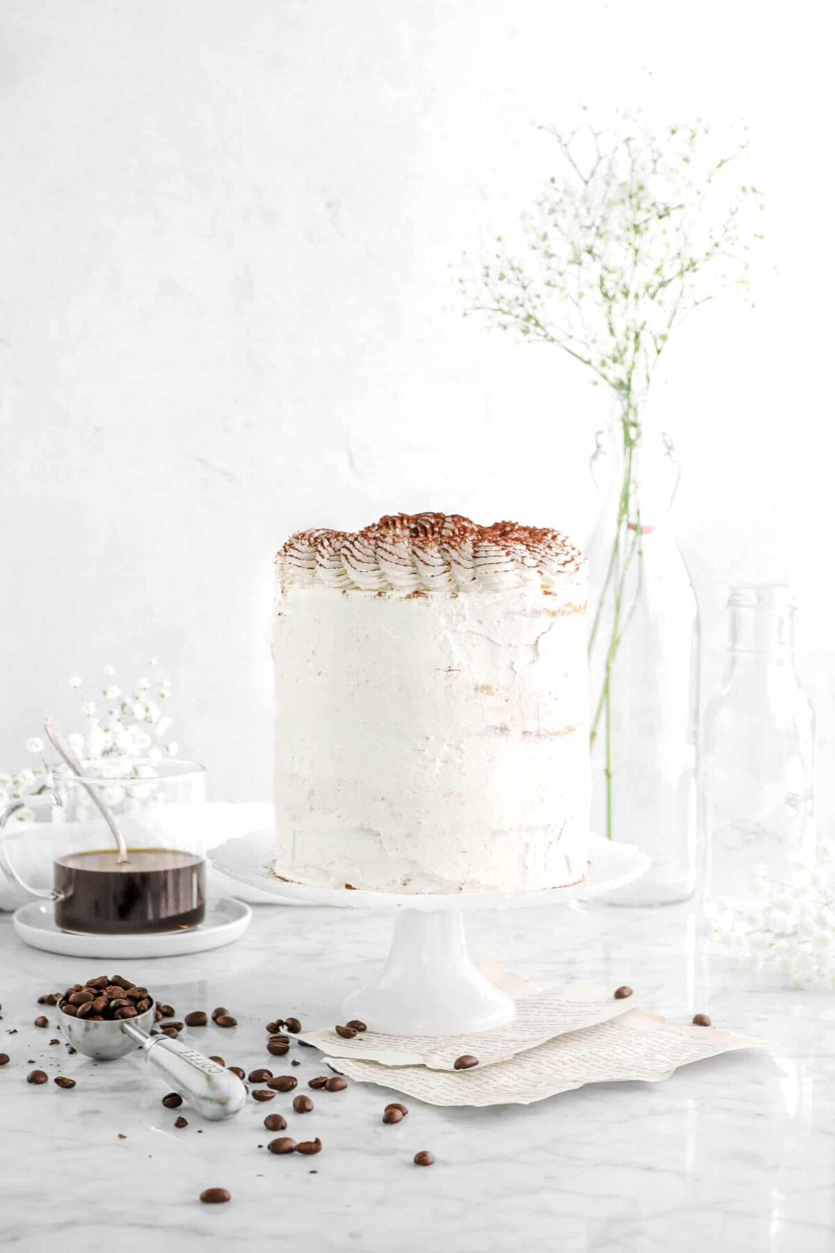 Tiramisu layer cake with coffee beans, flowers, and cup of coffee