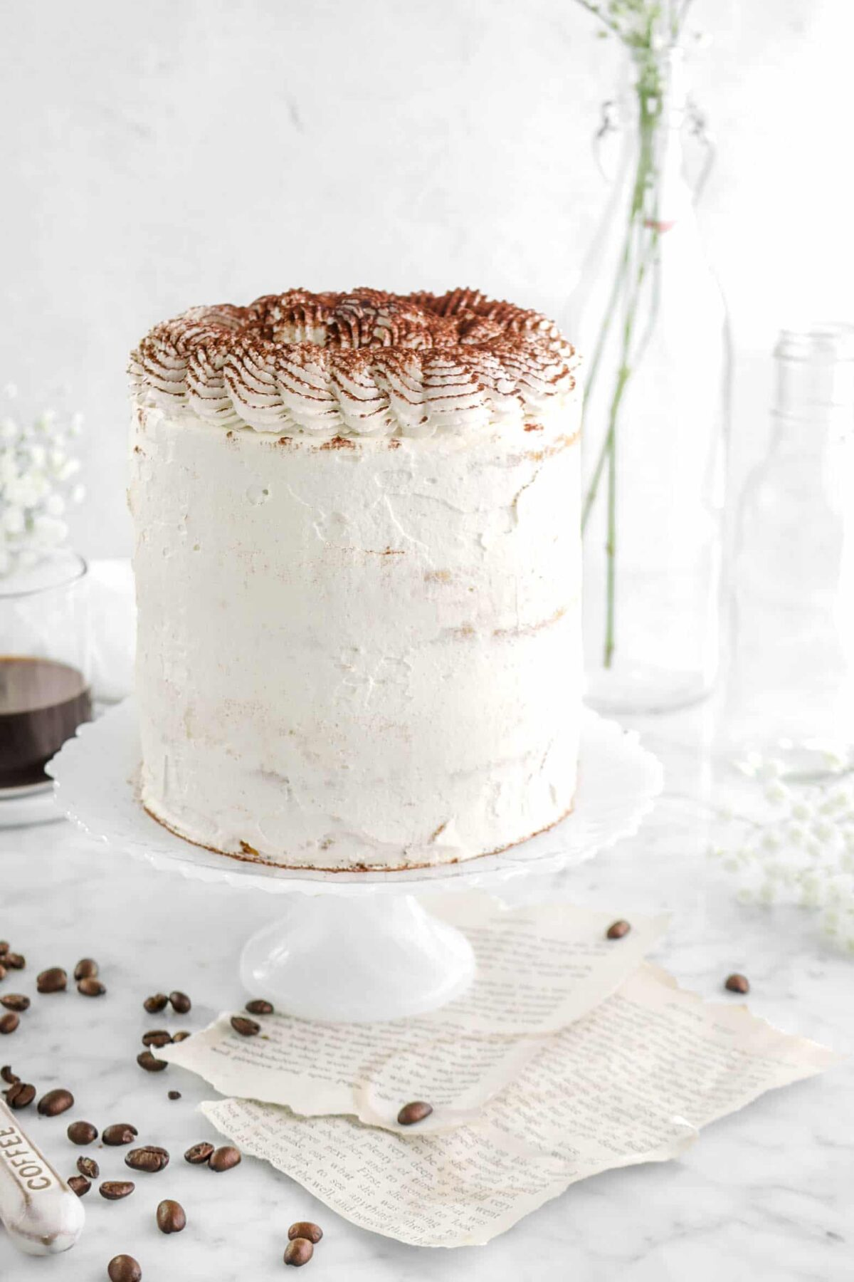 close up of tiramisu layer cake on white cake stand with book pages, flowers, and coffee beans