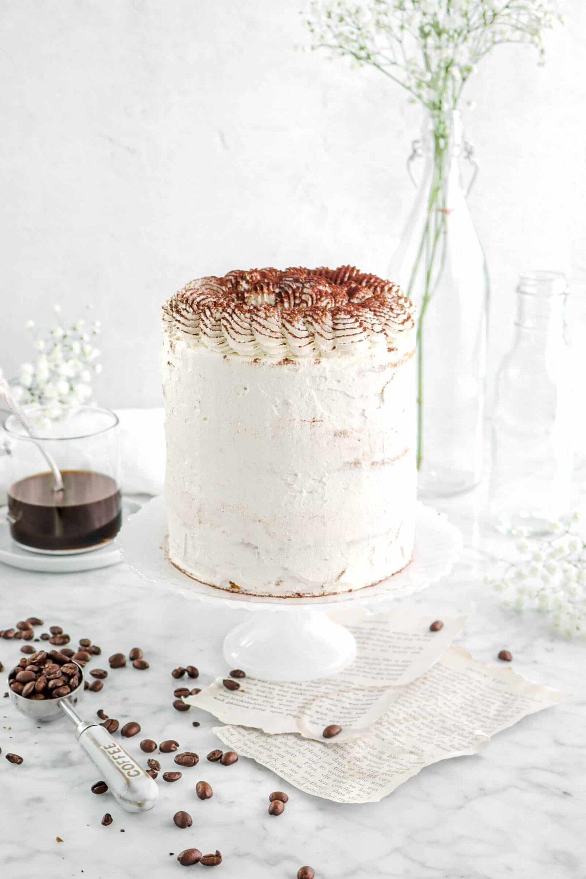 Tiramisu cake with flowers around, coffee beans, and a cup of coffee