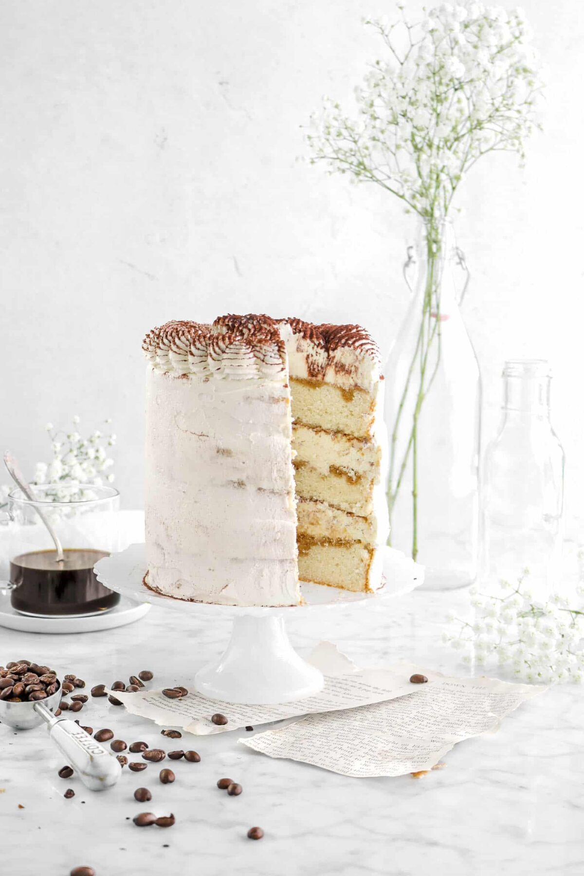 tiramisu cake with a slice missing, cocoa beans, flowers, and a cup of coffee