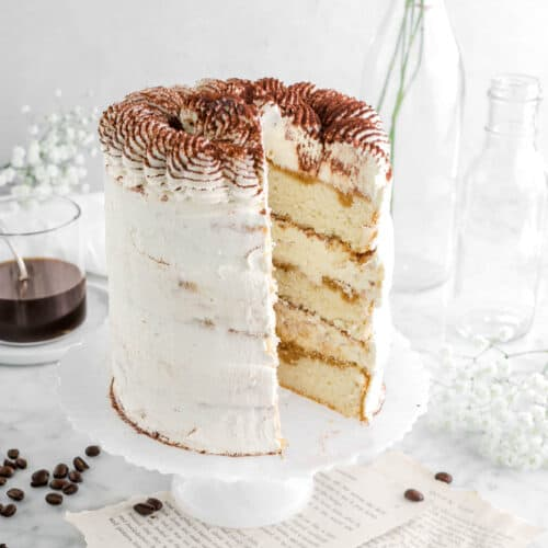 close up of cake with slice missing out of it on white cake stand