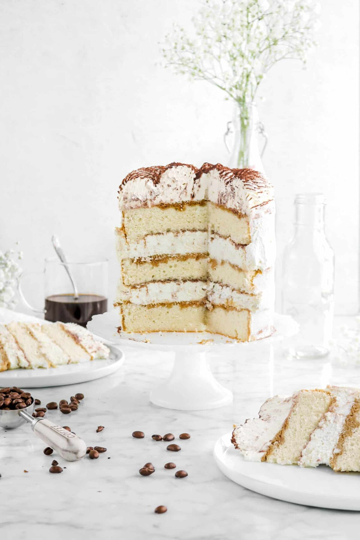 two slices of tiramisu cake on white plates in front and behind cake with coffee beans and flowers around
