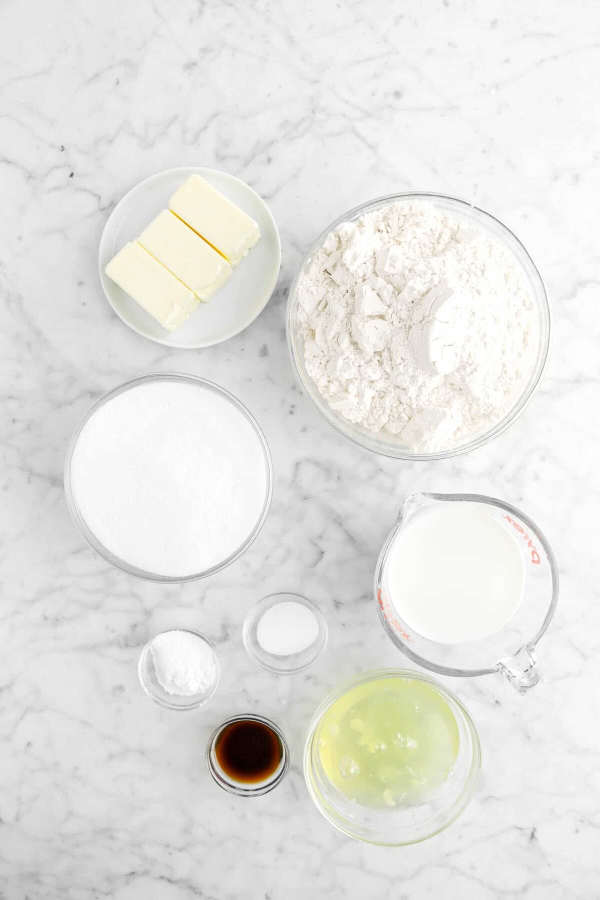 butter, flour, sugar, milk, baking powder, salt, vanilla, and egg whites on marble counter