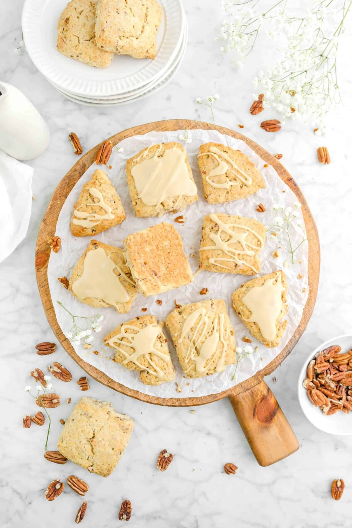 nine glazed maple pecan scones on wood board with flowers, pecans, and more scones around